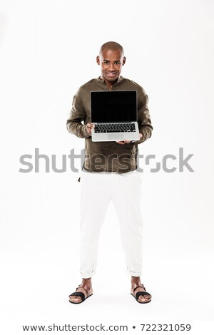 full length image of happy african man showing blank laptop computer stock photo © deandrobot
