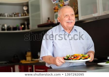 senior · uomo · sorridere · fotocamera · mangiare · insalata - foto d'archivio © is2