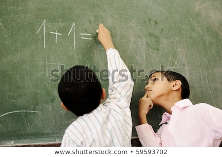 two boys in classroom thinking writing and counting on board stock photo © zurijeta