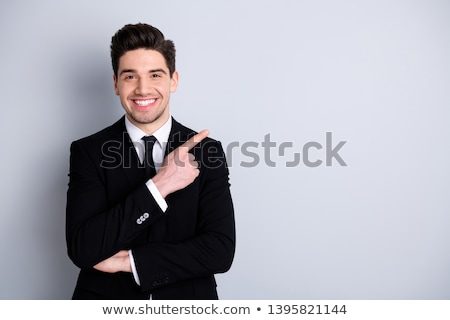 Close-up photo of young smiling man in formal wear pointing with Stock photo © deandrobot
