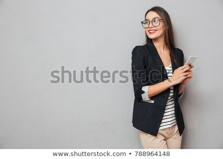 Smiling business woman in eyeglasses holding smartphone and looking back Stock photo © deandrobot