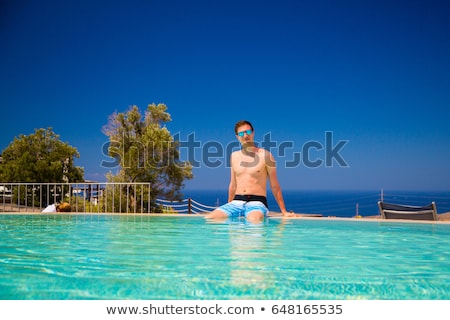 Couple sitting on the edge of pool Stock photo © IS2