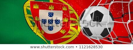 Soccer ball in goal net against digitally generated portugese national flag Stock photo © wavebreak_media