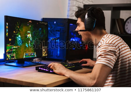 Portrait of angry gamer guy wearing headset yelling, while playi Stock photo © deandrobot