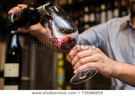 Man pouring red wine from bottle into a glass Stock photo © amok