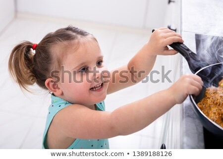 Pretty Girl Trying To Grab Hot Cooking Pan Stock photo © AndreyPopov