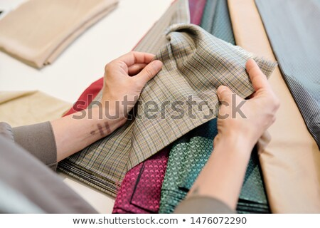 Human hands holding piece of fabric while choosing suitable one Stock photo © pressmaster