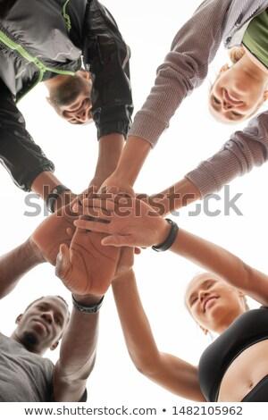 Group of young intercultural champions in activewear making pile of hands Stock photo © pressmaster