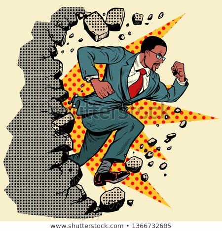 Leader african businessman breaks a wall, destroys stereotypes Stock photo © studiostoks