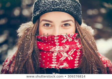 Sweet young woman in winter clothing looking up and smiling. stock photo © lichtmeister