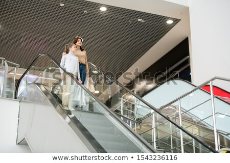 Young woman and her daughter with paperbags standing by escalator Stock photo © pressmaster