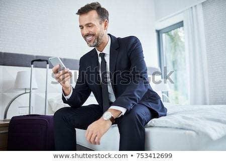 Elegant business traveler with smartphone and suitcase phoning hotel Stock photo © pressmaster