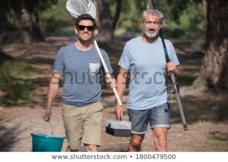 friends with fishing rods and net walking outdoors Stock photo © dolgachov