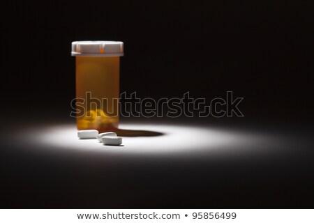 Medicine Bottle and Pills Under Spot Light stock photo © feverpitch