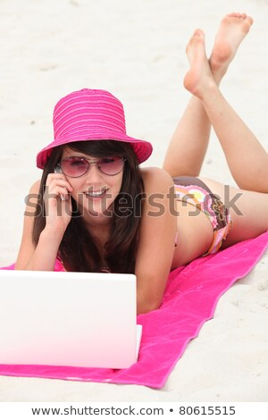 Young woman in a bright pink straw hat using her laptop computer on the beach Stock photo © photography33