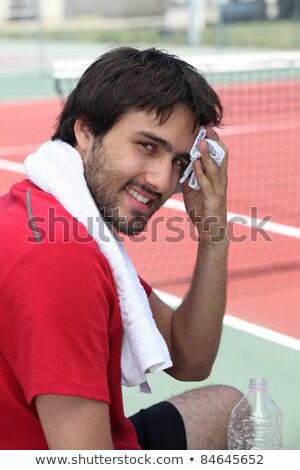 Tennis player mopping his brow on the sidelines Stock photo © photography33