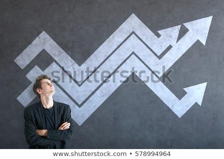 Atraente homem olhando mercado de ações gráficos símbolos Foto stock © ra2studio