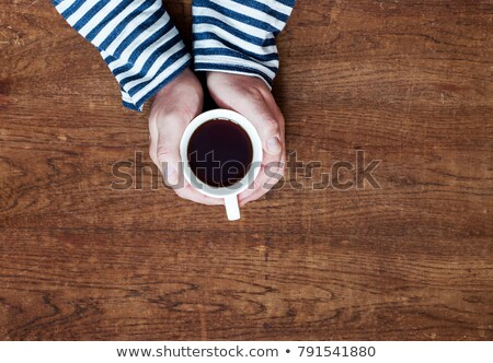 Womans and mens hands holding hot cup of tea Stock photo © artjazz