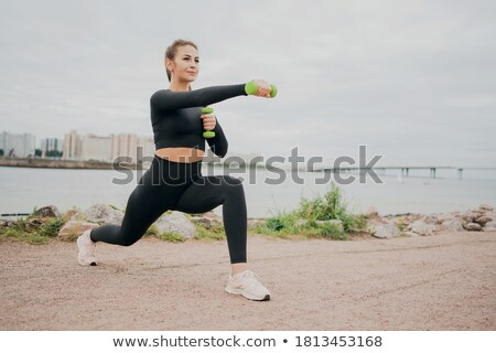 Young happy sport woman doing squats with dumbbells on gray background Stock photo © deandrobot