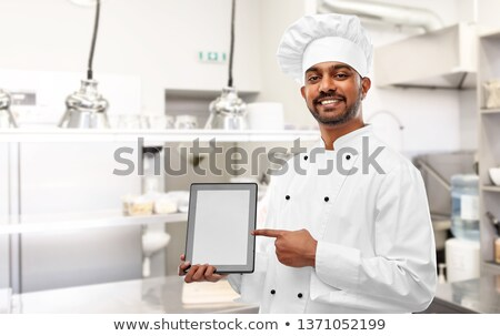 Stock photo: Happy asian man showing tablet computer screen over white background