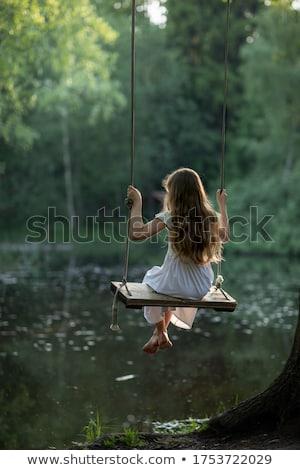 little girl swinging on a swing stock photo © superelaks