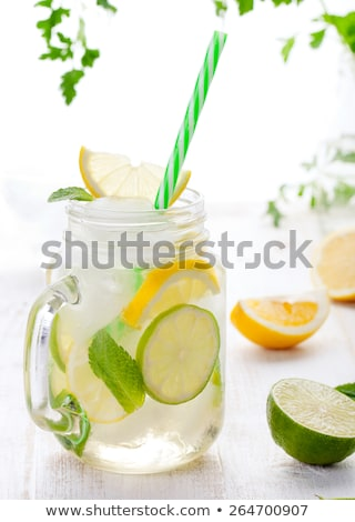 Lemon juice in glass jug and fresh fruits on white wooden background, vitamin drink or cocktail Stock photo © yelenayemchuk