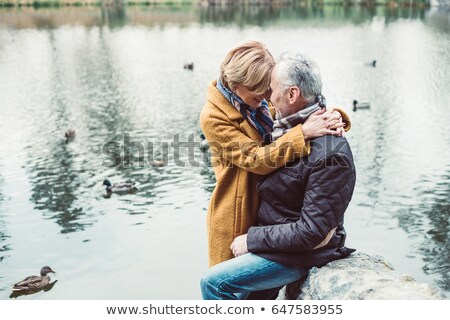 Senior woman standing by lake, side view Stock photo © IS2