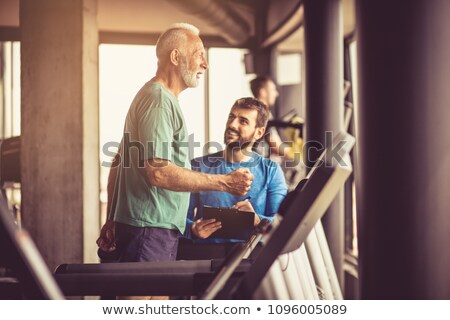 A personal trainer helping a man on a treadmill Stock photo © IS2