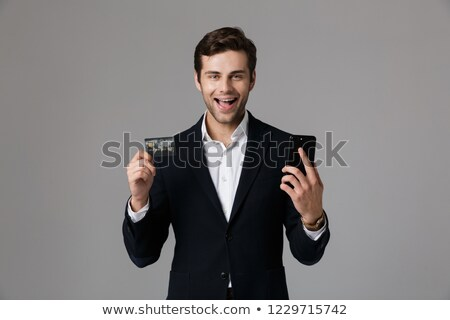 Image of delighted man 30s in business suit holding black mobile Stock photo © deandrobot