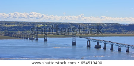 long suspension bridge spans the st lawrence river between montmorency and the scenic island of ile stock photo © lopolo