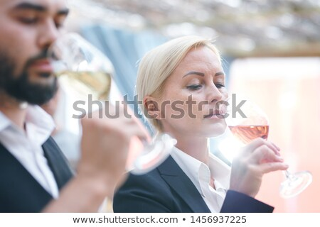 Blonde mature female sommelier smelling wine in wineglass Stock photo © pressmaster