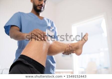 Young mixed-race physician holding sick leg of his patient while examining it Stock photo © pressmaster