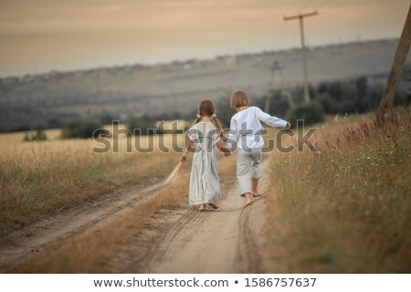 Two children running down a country road in shirt and dress Stock photo © ElenaBatkova