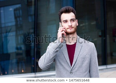Handsome young bearded businessman standing outdoors Stock photo © deandrobot
