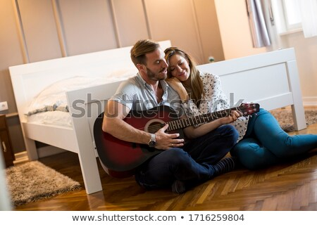 Man Playing Guitar And Woman Singing Song In Bedroom Stock photo © diego_cervo