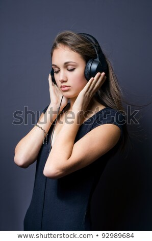gorgeous young brunette immersed in music stock photo © lithian