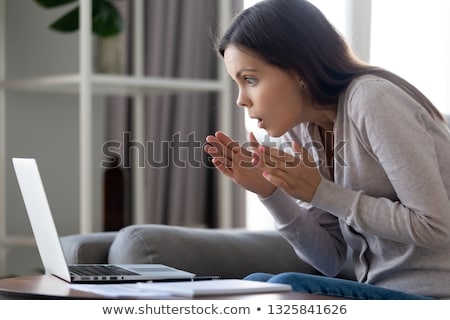 Young Woman Looking Surprised At Laptop stock photo © williv