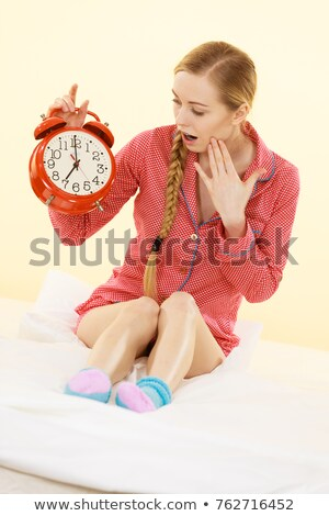 Young surprised woman holding a big clock stock photo © scornejor