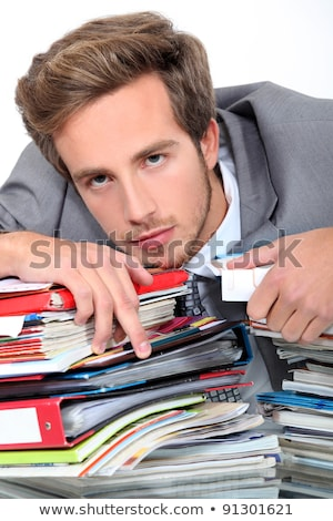 young man lying down on a desk full of binders and notebooks Stock photo © photography33
