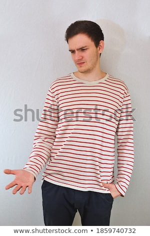 young man with hands tucked in pockets stock photo © feedough