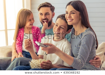 Smiling young woman using a tv remote stock photo © pablocalvog