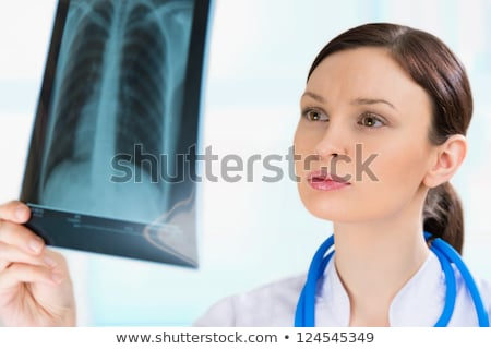 Female doctor looking at a lungs or torso xray, fluorography Stock photo © HASLOO