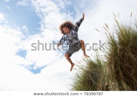 fiú · ugrik · tengerpart · fiatal · srác · felfelé · anya - stock fotó © monkey_business