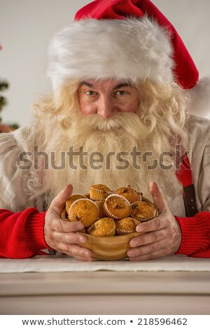 Santa Claus holding cookie or cupcake at home Stock photo © HASLOO