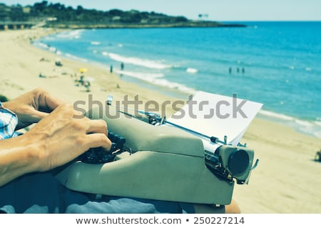 young man typewriting on the beach Stock photo © nito