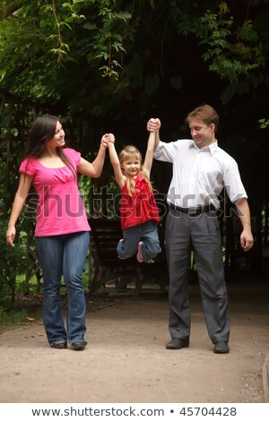 Little girl in red dress with father and mother in park. Girl plays being shaken on hands of parents Stock photo © Paha_L