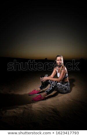 young pretty woman resting after training on beach at sunset stock photo © deandrobot