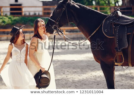 Stockfoto: Two Romantic Female Models Posing With A Horse