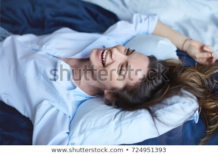 Smiling brunette woman lies on bed indoors Stock photo © deandrobot