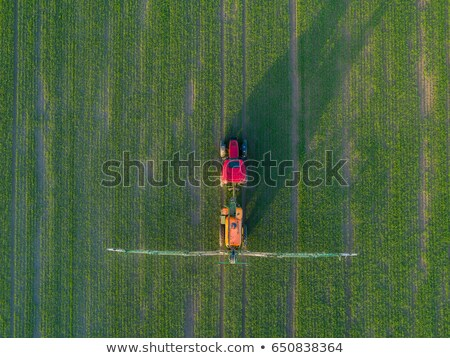 Aerial view of Tractor harvesting field tilling soil Stock photo © artjazz